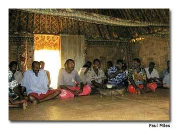 The men of the village conduct the Yaqona (kava) welcome ceremony inside the Chief's bure.